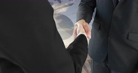 reaching : Close up of a handshake between businessmen with a background of a wide open field. Digital animation of graphs an statistics are running on the background 4k