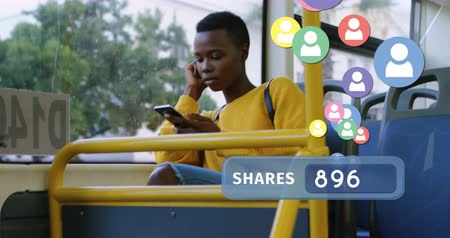 sociedade : Full view of an African-american woman seated on a bus while texting on her phone. Beside her is a digital animation of a shares count bar with profile icons flying upwards 4k Stock Footage