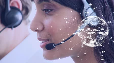 földgolyó : Close up of a female Indian call centre agent talking on her headset. Beside her is another male agent talking as well. Digital animation of a rotating globe with labels is seen in the foreground Stock mozgókép