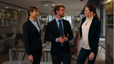 conta : Front view of a Caucasian businessman telling stories with two Caucasian female colleagues in an office library.