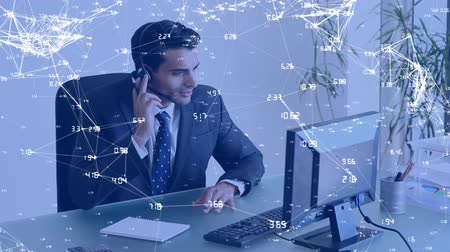 sofisticado : Full view of an Indian businessman wearing a headset talking over the internet on his computer. The foreground is filled with digital animation of labelled lines linked together Stock Footage