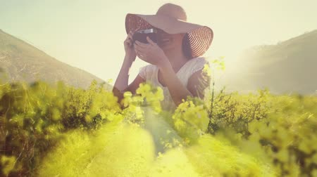 parkland : Front view of a Caucasian woman in a field of flowers taking pictures during a bright sunny day