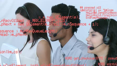 フォアグラウンド : Close up of a group of call centre agents talking on their headsets. Digital animation of program codes are running in the foreground