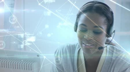 kapatmak : Close up of an African-american female call centre agent talking on her headset. Digital animation of lines and graphs are running in the foreground Stok Video