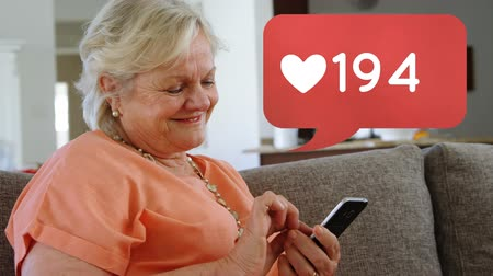 обмен сообщениями : Close up of a Caucasian old lady sitting on the couch while browsing on her phone. Beside her is a digital animation of message bubble with a heart icon increasing in count. Стоковые видеозаписи