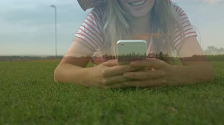 interativo : Close up of a woman lying on a field of grass while texting on her phone Stock Footage