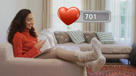 обмен сообщениями : Digital composite of Caucasian woman on a couch while texting on her phone. In the foreground is an animation of a heart icon with number count up Стоковые видеозаписи