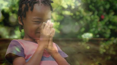 dua eden : Digital composite of an African-american little girl praying in the woods on a bright sunny day Stok Video