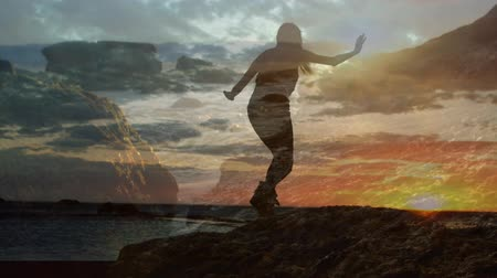 harness : Silhouette of a woman climbing rocks beside ocean with a view of the sunset Stock Footage