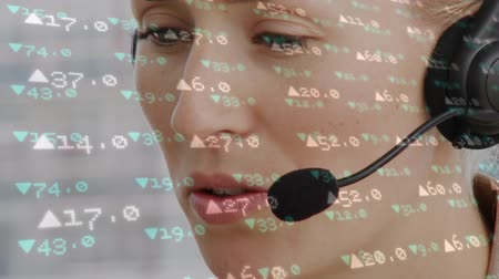 etkileşim : Digital composite of Caucasian female call centre agent working and stock market numbers Stok Video