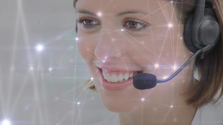 оператор : Digital composite of female Caucasian call centre agent working and connected lines and dots can be seen in the foreground Стоковые видеозаписи