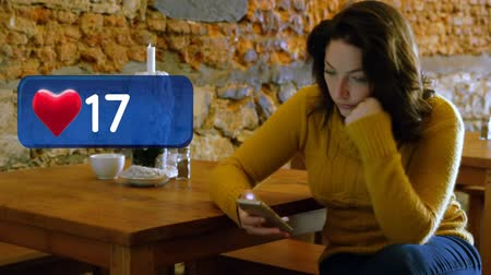 representação : Digital composite of a woman texting in a restaurant and a heart icon increasing in count Vídeos