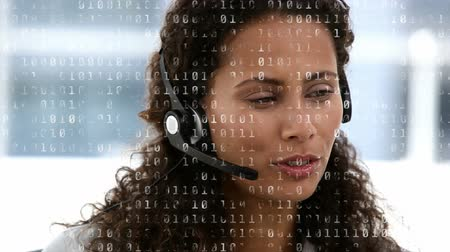 кодирование : Digital composite of a Caucasian call centre agent talking to a client and binary codes running in the foreground Стоковые видеозаписи