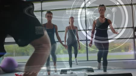 atom : Digital composite of three women doing aerobics at gym with male instructor. DNA helix and multiple circles with labels are seen in the foreground