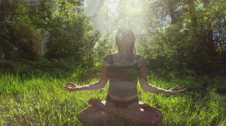 content : Front view of a woman meditating in the forest sitting on grass. Behind her are trees