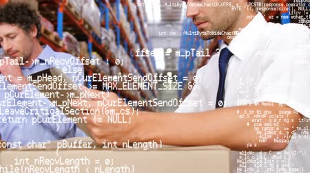 tektura : Close up of two Caucasian male warehouse managers checking on packages in the warehouse. One of them looks at the camera smiling. Program codes are seen running in the foreground
