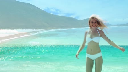 пляжная одежда : Full view of a Caucasian woman wearing a bikini dancing on the beach