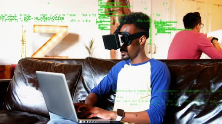 command : Digital composite of an African-American adult male wearing virtual goggles and using a laptop on the couch while a man uses a tablet behind him and foreground shows green digital codes.