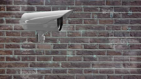 csatolt : Digitally generated animation of a surveillance camera attached on a brick wall with digital codes and security warnings in the foreground. Stock mozgókép