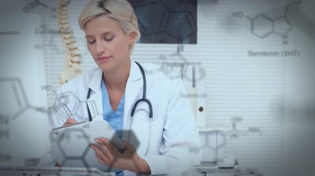 kimyager : Digital composite of a Caucasian female doctor writing while sitting behind desk and chemical structures move in the foreground. Stok Video