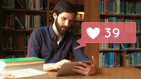knihkupectví : Digitally generated animation of a message bubble icon with a heart and increasing numbers while background shows a Caucasian man using a tablet inside a library. Dostupné videozáznamy