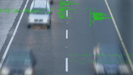 command : Digital animation of program codes in the screen while background shows a time lapse of a busy road with cars.