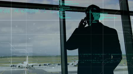 tárcsázás : Digital composite of a silhouette of a man while using a cellphone in an airport while program codes move in the foreground.