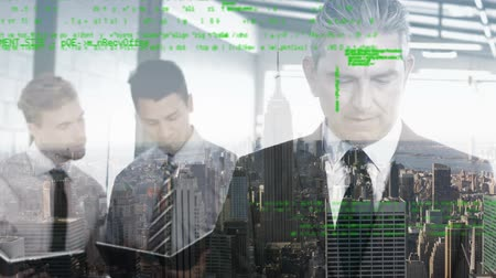 kifinomult : Digital composite of Caucasian businessmen in an office with program codes moving in the foreground and a view of the city in the background. Stock mozgókép