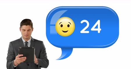 kifinomult : Digital composite of a Caucasian businessman in suit using a tablet with a winking emoji with increasing numbers 4k Stock mozgókép