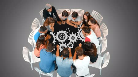 etkileşim : Digital composite of a diverse group of people seated in a round table looking a gears moving. Stok Video