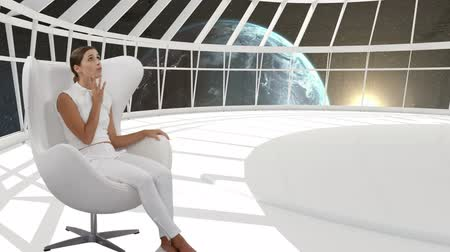 astro : Digital composite of a Caucasian woman sitting in a white room while earth is visible in the background