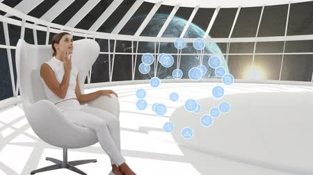 descarregamento : Digital composite of a Caucasian woman sitting in a white room with view of the earth on the window while digital app icons arranged spherically expands in the room