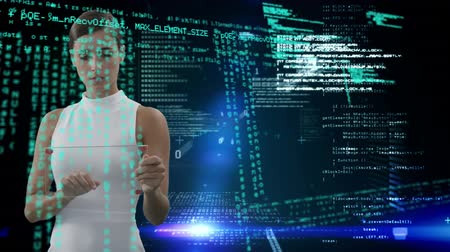 comando : Digital composite of a Caucasian female using a futuristic tablet while program codes and glowing lights move in the screen