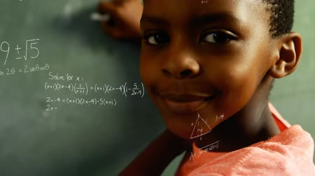 hesaplamak : Digital composite of an African-American boy holding a chalk at the board while mathematical equations move in the screen