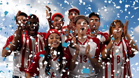estádio : Digital composite of a group of diverse fans wearing uniforms cheering while confetti fall