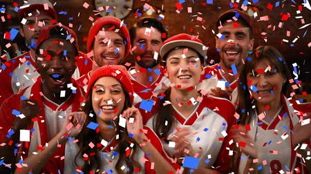 fiesta : Digital composite of a group of diverse fans wearing uniforms cheering while confetti fall