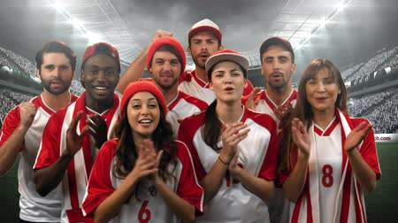 começando : Digital composite of a group of diverse fans wearing uniforms cheering in a stadium