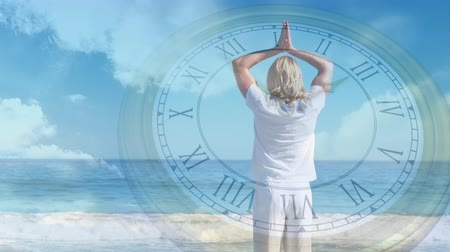 dia : Digital composite of a Caucasian man doing yoga by the beach while background shows the sky with clouds and analog clock Vídeos