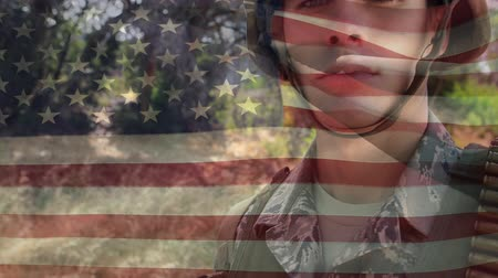 patriota : Digital composite of a Caucasian military man in uniform while American flag waves in the background