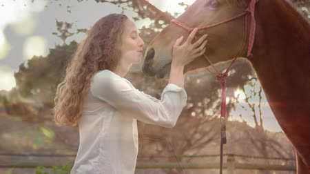 juba : Digital composite of a Caucasian woman kissing a brown horse in a farm Stock Footage