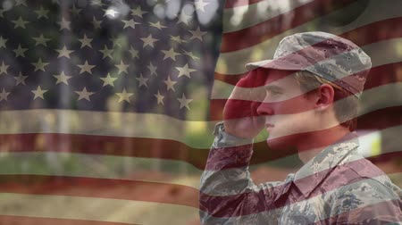 amerikan : Digital composite of a military man saluting while in the park and American flag waving in the background Stok Video
