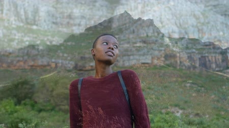 fogaskerekek : Digital composite of an African-American woman standing on a mountain side Stock mozgókép