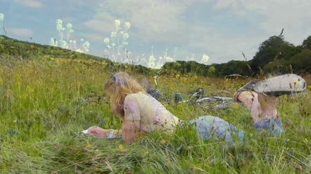 istálló : Digital composite of a Caucasian woman lying on the grass while writing with background of field of flowers Stock mozgókép