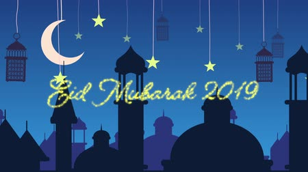 hilâl : Digitally generated animation of a gold glitter Eid Mubarak greeting for 2019 with a blue background of mosque silhouettes and black lanterns hanging with yellow stars and crescent moon in white Stok Video