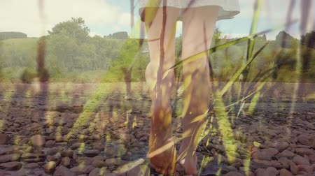 abandonment : Digital composite of a girl walking barefoot on a rocky river bank with tall grass in the foreground
