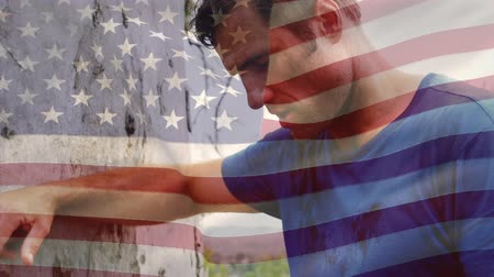 spangled : Digital composite of a Caucasian man leaning on a tree trunk with an American flag waving in the foreground