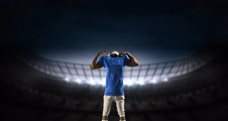 dobrar : Rear view of an American football athlete limbering up preparing to enter a digital stadium 4k