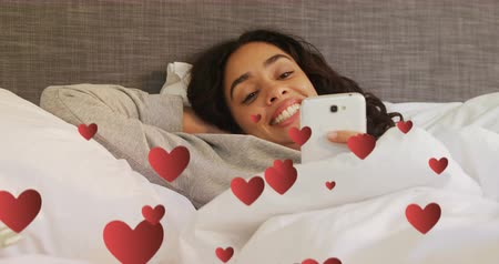 příloha : Digital composite of a Hispanic woman lying in bed smiling while texting and digital hearts flying in the foreground 4k