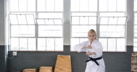 истребитель : Front view of a Caucasian female black belt displaying her skills in a gym 4k