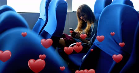 plavé vlasy : Digital composite of a Caucasian woman sitting and texting in a bus and digital hearts flying in the background 4k